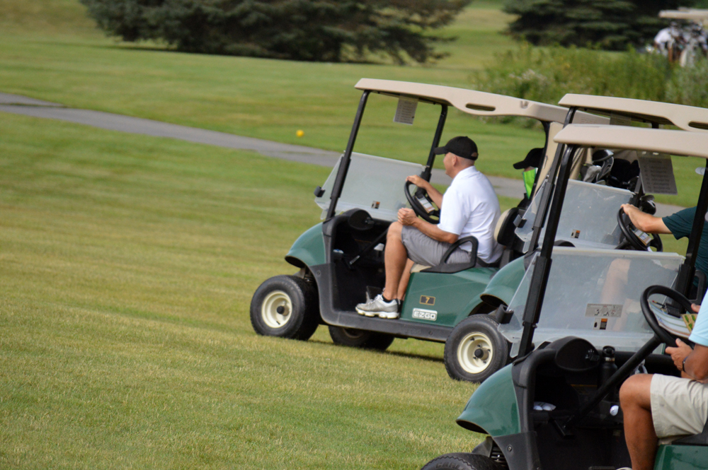 Photo of Chris Melde Driving a Golf Cart